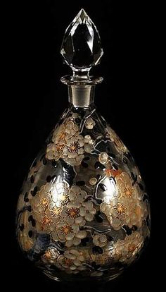 Delvaux Perfume Bottle, ca. 1920…clear blown glass bottle with ground and polished pontil bottom, decorated with black, white and gilt blossoming branch overall decoration.