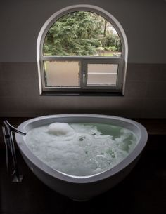 Bijzonder gevormd bad van Hansgrohe met een staande badkraan.