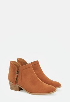 A faux suede bootie featuring a decorative zipper accent and dual side curved edges.  ...