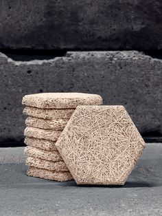 raw woolwood cement board hexagonal discs used in the studio of Swedish design group Form Us With Love. The process of making wood wool cement is quite simple: wood slivers is cut from logs, then mixed with water and cement and put in a mould to dry into shape. The result is a material that is environmentally friendly, water resistant, moisture and sound absorbant.