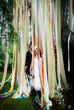 colorful ribbon backdrop mixed with the natural greenery. great for a photo booth!