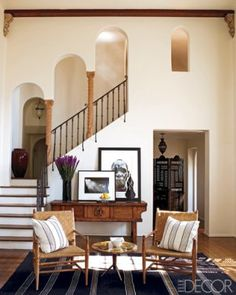 Mediterranean touches abound in the living room, including Moroccan-style arches framing the staircase and breezy cotton textiles used for the pillows.