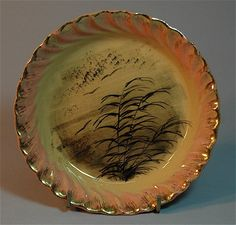 "Early Rookwood Pottery scenic pie plate, 6.5"" dated 1882, shape 140, by Martin Retting. Twisted scalloped edge with gold trace decoration. Impressed Rookwood logo. Good condition with 2 tiny flecks at rim edge."
