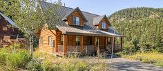 Log cabin in Salt Lake surrounded by green disiduous trees in Big Cottonwood Canyon near Brighton and Solitude