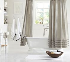 A freestanding tub makes this all white bathroom feel extra luxurious! Plus, how cute is this striped and ruffled shower curtain?