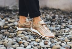 The women's Nike Air Max 97 Ultra in Metallic Red Bronze is featured in a lifestyle look.