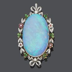 An opal, demantoid garnet, ruby and diamond pendant, circa 1900 Set to the centre with a large oval cabochon opal, within an openwork foliate border of demantoid garnet clovers, alternating with ruby and diamond floral clusters and diamond set leaves, to ribbon bow terminals set with old brilliant-cut diamonds, pendant length 6.2cm.