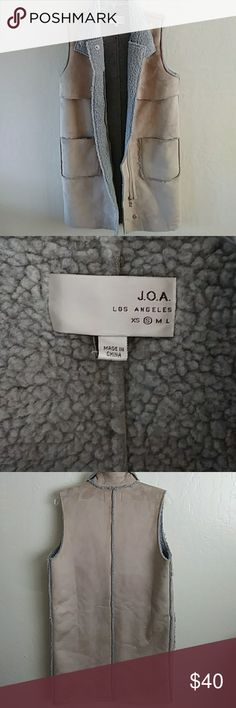 """J.O.A Los Angeles sz S  sleeveless sherpa vest Tan and Grey long sleeveless faux suede and faux sherling vest by J.O.A Los Angeles.  Great piece fun, unique and on trend. 2 square pockets on front of vest to warm cold hands . The length of th vest from top of the shoulders is 36 1/2"""", from underneath the arm down is 26"""" Dry clean only J.O.A Los Angeles Jackets & Coats"""