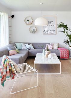I like the pastel colours used in the space. Really like the large grey lounge. the room has been styled well