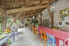 Mismatched different coloured wooden chairs create a quirky look in the summer kitchen at Maison Lacombe, self-catering holiday property in SW France, sleeps 12. www.purefrance.com