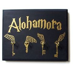"""Hand Painted Harry Potter Alohomora Key Holder by WillowAndRoxas on Etsy for $20.00 USD. This is a wooden key holder with 4 metal hooks. It is hand painted with deep dark blue and metallic gold paint to have flying keys and """"Alohomora"""" on it. The wood will have a protective coating to prevent major scratches. There's small picture frame hook on the back to hang on a wall. 