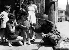 A WAC (Woman Army Corps), shares chocolate with small children in Carentan 1944