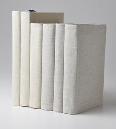 Fabric wrapped books in linen- how perfect would these be in a beach house?