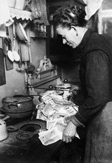 A woman burning money on a stove