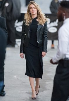 Look da atriz Amber Heard com vestido preto midi e jaqueta de couro.