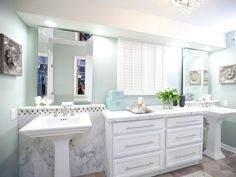 The bathroom is given a timeless update with classic black-and-white marble tile, dual pedestal sinks and neutral tile flooring. Valspar Jekyll Grand Dining Sea Mist paint freshens up the space and contributes to the room's tranquil, spa-like feel.