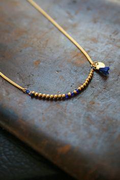 Un collier tout en délicatesse, doré à l'or fin, orné de perles or sur un fils de soie, rehaussé de perles indigo ou rouge  et de pampilles (un sequin et un pompon accordé au tube coloré). Merci...