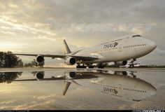 Amazing scene and gorgeous reflections in the water of a Thai Airways International B747-4D7 Parked at Phuket Int'l Airport