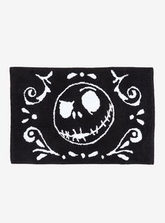 """Oh how awful your bathroom will look with this bath rug from  The Nightmare Before Christmas ! The black and white tufted rug features Jack's scary face with filigree details.    100% cotton  Wash cold gentle cycle; dry low  20"""" x 30""""  Imported"""