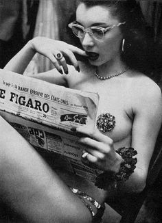 A showgirl reading newspaper at the backstage of Moulin Rouge, Paris, 1956