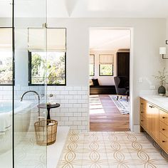White bathrooms just feel cleaner. A buff motif on the concrete-tiled floor pulls its sandy shade from the white oak vanity.