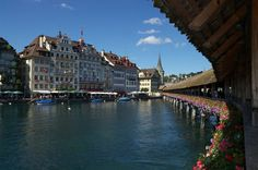 Lake Lucerne, Switzerland.Stayed at hotel near this bridge and market place.  Got up early to take pic in early morning light.  Swans were gliding by under the flowers.  Breathtaking.  One of the prettiest single spots I have seen any where in the world.