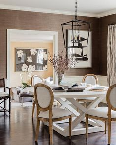 Clad in brown grasscloth wallpaper lined with white wainscoting, this stunning white and brown dining room is illuminated by a Darlana Medium Lantern hung above a round white dining table surrounded by French round back dining chairs.