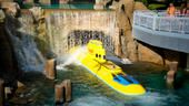 A Finding Nemo Submarine Voyage vehicles travels under a waterfall