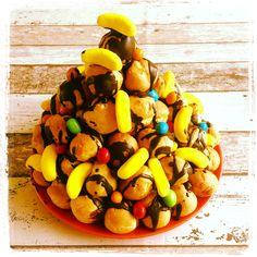 Slagroomsoesjes,met chocoladesaus en versierd met snoepjes.