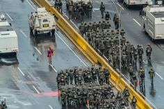 A lone violinist playing in front of riot police officers in Venezuela