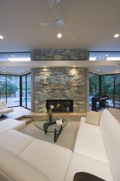 Bright white U-shaped sectional wraps around oblong glass coffee table in front of large stone-wall fireplace in this glass-surrounded living room.