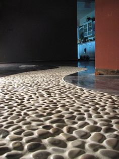 inlaid river rock. i'd do it outside though. reminds me of the floors of the old castles we saw in Spain!