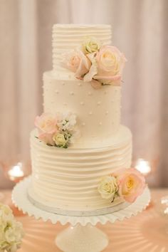 Classic simple white wedding cake with small icing dotted and rose accents
