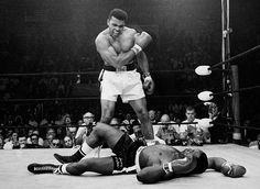 Lewiston, Maine — On May 25, 1965, heavyweight champion Muhammad Ali stands over fallen challenger Sonny Liston after dropping Liston with a short hard right to the jaw. Ali had upset Liston to win the title 15 months before.