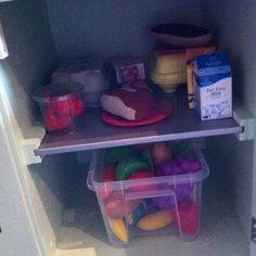 Play kitchen fridge stocked with goodies, felt, plastic fruit and veg and cartons.