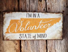 "$38-""I'M IN A Volunteer STATE of MIND"" is a wood sign on 30 yr old recycled Tennessee barn wood. * White hand painted background with orange Tennessee state and white text * Size: 18"" X 8"". * This sign will look great in any fans home...from the den to the game room to the office, this is sure to show your pride for your team or your love for the great state of Tennessee!"