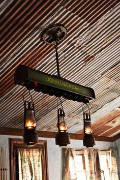 Old Rustic John Deere Lantern Chandelier is awesome against the old corrugated metal ceiling. Lantern Chandelier, Red Lantern, Lantern Lighting, Cabin Chandelier, Pipe Lighting, Patio Lighting, Kitchen Lighting, Metal Ceiling, Metal Roof