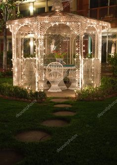 A white wicker gazebo with chairs and a table is lit up at night by several small white lights