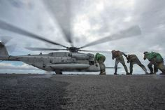 Marines lean into the rotor wash of a CH-53E Super Stallion as it takes off from the flight deck of the USS Bonhomme Richard in the South China Sea, Oct. 6, 2016. The amphibious assault ship is supporting security and stability in the Indo-Asia-Pacific region. Navy photo by Petty Officer 2nd Class Diana Quinlan