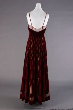 Evening Dress, 1940. Patou, Jean, 1887-1936. Dress of wine-colored velvet with intertwining serpentine cut-out design over wine net; gold/navy blue lame shows through cut-outs. Serpentine figuring is smaller at bustline and larger at hem. Heart-shaped bodice with spaghetti straps and raised waistline. Machine and hand sewn. Clothing label on dress: Jean Patou/PARIS. Back