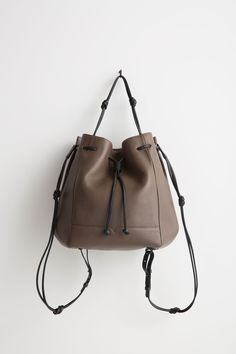 The @vonholzhausen Bucket Backpack in Taupe made from natural grained soft Italian leather with painted edges. Removable straps allow the bag to be worn as a backpack, shoulder bag, or handheld.