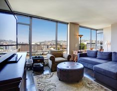 Floor to ceiling glass all around illuminates this rich textured living room, allowing expansive views over the surrounding city. Dark hardwood flooring, circular button tufted leather ottoman, and blue L-shaped sectional stand out in the space.