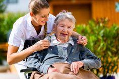 silla de ruedas: Mujer mayor en un hogar de ancianos con la enfermera en el jardín sentado en silla de ruedas