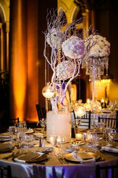 Beautiful tall centerpiece with white and lavender flower kissing balls draped from whimsical branches.
