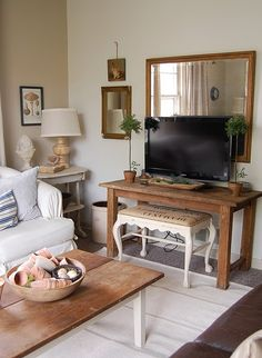 interesting concept - hang a mirror behind the flatscreen to reflect light and draw attention away from the tv.