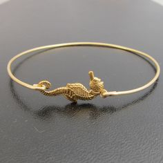 Seahorse Bangle Bracelet Gold by FrostedWillow on Etsy. $16.95, via Etsy. WANT THIS