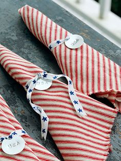 """""""Stars & Stripes  Salute Old Glory with star-studded napkin rings. Stamp """"USA"""" into metal tags using a steel stamp set. Thread star-print ribbon through the tags and wrap around striped napkins. For no-sew napkins, cut cotton ticking in 16-inch squares; fray the edges by pulling on the threads."""""""