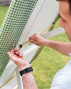Use bungee cords and grommets to keep a tablecloth from billowing in the breeze.Cut oilcloth to the length of a rectangular table (or 4 to 6 inches shorter, as we did) and to the width plus 16 inches. Pink or hem the short edges.Tools and MaterialsOilcloth, in Green Gingham, from Oilcloth International; oilcloth.comScissorsPinking shears1-inch grommet kit (including 6 grommets, a cutting block, a hole cutter, and an insert punch)HammerThree 12-inch bungee cords, in various colors, 10003...