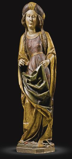 GERMAN, MIDDLE RHINE OR FRANCONIA, CIRCA 1490 FEMALE SAINT with remnants of an old label with Gothic lettering to the top of the head, and a label numbered: 133. on the reverse gilt and polychromed limewood, on a wood base 134.5cm., 53in. overall