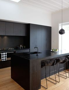 A matte black kitchen makes a bold statement in this Auckland villa